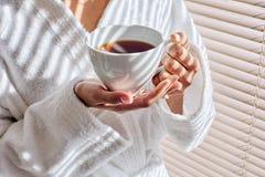 Manos femeninas que sostienen una taza de t? imágenes de archivo libres de regalías