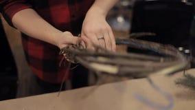 Manos femeninas que tejen la barra de madera del corte de la guirnalda con los alicates