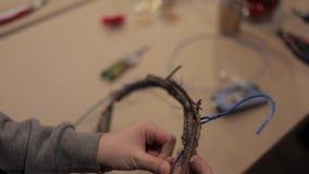 Manos femeninas que tejen la guirnalda con barras de madera y un alambre azul flexible