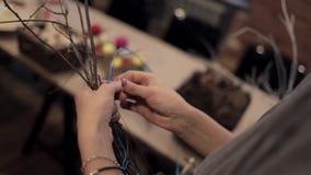 Manos femeninas que tejen la guirnalda que corta el alambre con los alicates