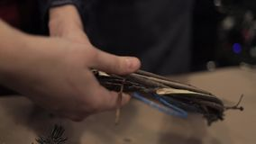 Manos femeninas que tejen la guirnalda de la barra de madera en el alambre flexible