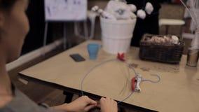 Manos femeninas que tejen la guirnalda que sostiene un alambre azul flexible