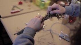 Manos femeninas que tejen la rama seca de vacilación del pino de la guirnalda en un alambre