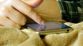 Manos femeninas que tocan smartphone mientras que miente en la hoja de cama imágenes de archivo libres de regalías
