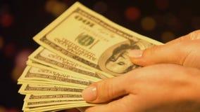 Manos femeninas que toman el manojo de dólares, contando el dinero, comercio ilegal del negocio metrajes