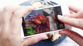 Manos femeninas que toman la foto de la comida del almuerzo del vegano en el teléfono móvil para medios social o que bloguean metrajes