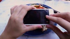 Manos femeninas que toman la foto de la comida del almuerzo del vegano en el teléfono móvil para medios social o que bloguean almacen de video