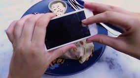 Manos femeninas que toman la foto de la comida del almuerzo del vegano en el tel?fono m?vil para medios social o que bloguean metrajes