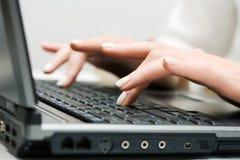 Manos femeninas que trabajan en la computadora portátil. Imágenes de archivo libres de regalías