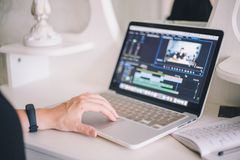 Manos femeninas que trabajan en un ordenador portátil en un programa que corrige video fotos de archivo