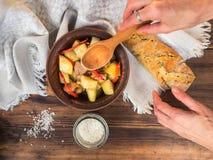 Manos femeninas servidas la tabla Aún vida rural de patatas cocidas con la carne en un cuenco de cerámica Pan y sal en Imágenes de archivo libres de regalías