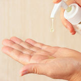 Manos femeninas usando el jabón líquido cosmético Fotografía de archivo