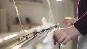 Manos femeninas usando la máquina para hacer punto para el modelo que teje en taller almacen de video