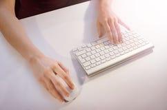 Manos femeninas usando ratón y el teclado foto de archivo libre de regalías