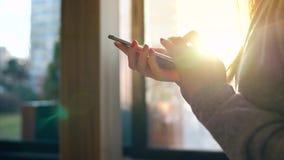 Manos femeninas usando smartphone contra un paisaje urbano borroso en el sol poniente