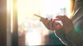 Manos femeninas usando smartphone contra un paisaje urbano borroso en el sol poniente metrajes