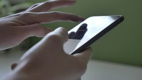 Manos femeninas usando smartphone negro grande, una tabla soleada en el fondo, cierre encima de 60 fps almacen de metraje de vídeo