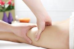Manos fuertes que trabajan en las piernas para dar masajes a las celulitis Fotos de archivo