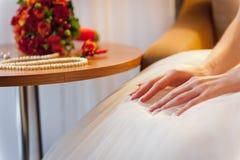 Manos hermosas blandas en el vestido de boda blanco elegante Imagen de archivo