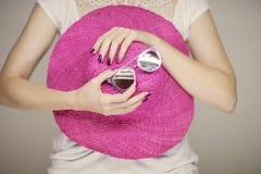 Manos hermosas de la mujer con el esmalte de uñas rosado perfecto que sostiene el sunhat y las gafas de sol, humor feliz de la pl foto de archivo libre de regalías