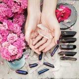 Manos hermosas de la mujer con el esmalte de uñas violeta perfecto en el fondo de madera blanco que sostiene pocos cristales de c foto de archivo