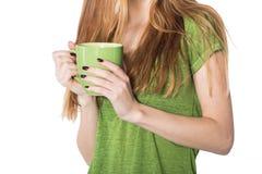 Manos hermosas de la mujer que sostienen la taza de café verde foto de archivo libre de regalías