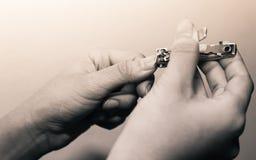 Manos hermosas de la mujer usando el cortador del clavo para las uñas cortadas en c Fotografía de archivo