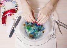 Manos hermosas del ` s de la mujer con la manicura en el cuenco de agua Imagen de archivo