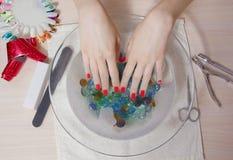 Manos hermosas del ` s de la mujer con la manicura en el cuenco de agua Imagenes de archivo