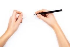 Manos humanas con el lápiz y la escritura de goma del borrado algo imágenes de archivo libres de regalías
