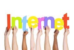 Manos humanas diversas que llevan a cabo Internet de la palabra Fotografía de archivo