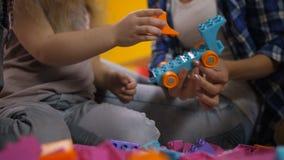 Manos humanas que crean los juguetes de bloques del constructor almacen de metraje de vídeo