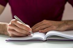 Manos humanas que escriben en el cuaderno encima de la tabla Fotos de archivo