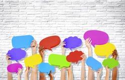 Manos humanas que llevan a cabo burbujas coloridas del discurso Imágenes de archivo libres de regalías