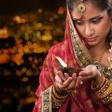 Manos indias de la muchacha que sostienen la lámpara de aceite del diwali