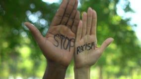 Manos interraciales de la gente que aparecen con la frase del racismo de la parada, discriminación metrajes