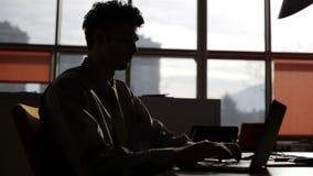 Manos jovenes del hombre de negocios que mecanografían en el ordenador portátil almacen de metraje de vídeo