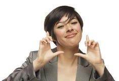 Manos jovenes sonrientes de la mujer adulta de la raza mixta que enmarcan la cara Imágenes de archivo libres de regalías