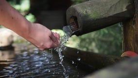 Manos lavadas en agua potable en la fuente de madera metrajes