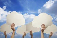 Manos múltiples que sostienen las nubes de papel cortadas contra un cielo azul con las nubes Imagen de archivo libre de regalías