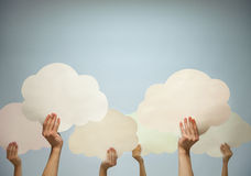 Manos múltiples que sostienen las nubes de papel cortadas contra un fondo azul, tiro del estudio Fotografía de archivo