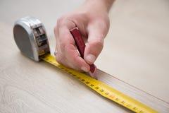 Manos masculinas con la cinta métrica y el nuevo piso de madera laminado imagen de archivo