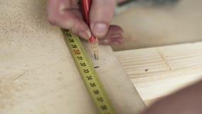 Manos masculinas con la regla amarilla y el lápiz rojo que hacen marcas en tablón de madera metrajes