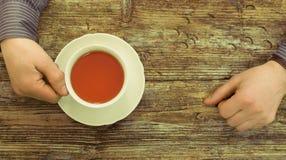 Manos masculinas de madera de la tabla del café que llevan a cabo la opinión superior de la taza de té Imagenes de archivo