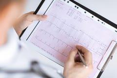 Manos masculinas del doctor con el cardiograma Imágenes de archivo libres de regalías