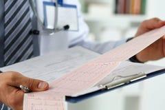 Manos masculinas del doctor de la medicina que llevan a cabo la carta del cardiograma Fotografía de archivo