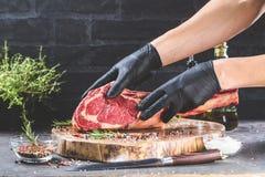Manos masculinas del filete de carne de vaca de la hacha de guerra de la tenencia del carnicero o del cocinero en fondo rústico o imagenes de archivo