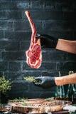 Manos masculinas del filete de carne de vaca de la hacha de guerra de la tenencia del carnicero o del cocinero en fondo rústico o fotografía de archivo libre de regalías