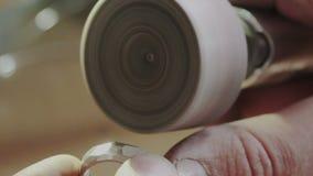 Manos masculinas del joyero usando la herramienta rotatoria de la mano profesional para pulir una joyería del anillo de oro del d almacen de metraje de vídeo