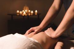 Manos masculinas del primer que hacen masaje curativo con aceite a una chica joven en una oficina oscura de la cosmetología Llave fotografía de archivo